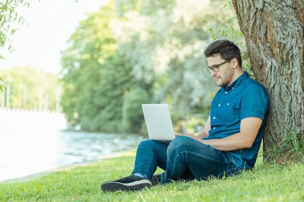 自然の中で屋外に座ってラップトップを持つ男