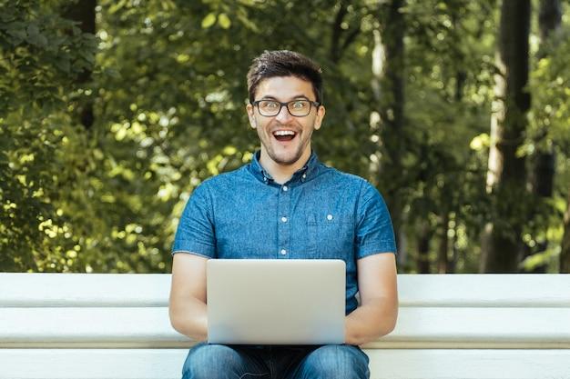 公園に座ってノートを持つ若い男