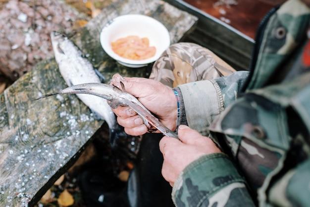 屋外で木の板に魚を洗浄する漁師