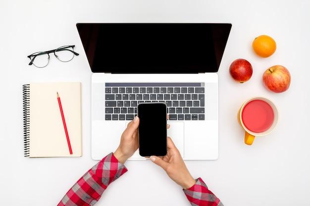 女性は白いオフィスの机の上の空白の画面でスマートフォンを使用しています