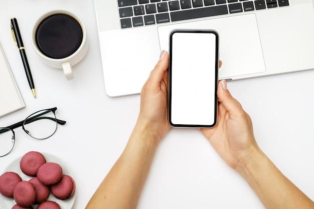 空白の画面で携帯電話を押しながら使用する女性の手の画像のモックアップ