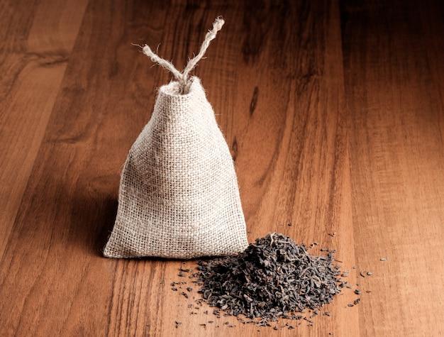 木製の背景にお茶とビンテージの黄麻布