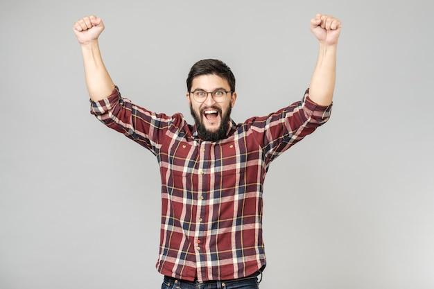 Счастливый бородатый человек, поднимая руки, показывая жест победы