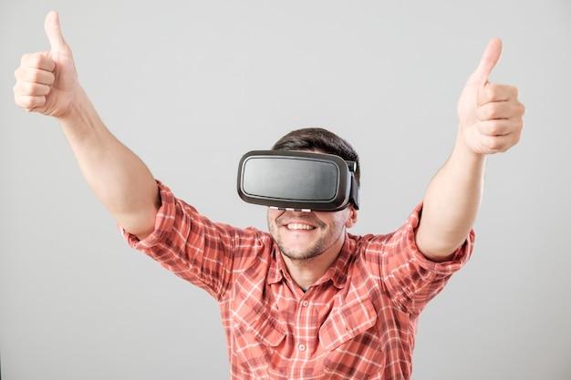 親指を現して仮想現実の眼鏡を持つ男