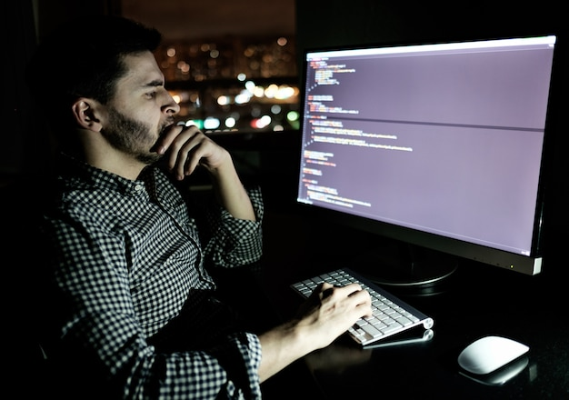 暗いホームオフィスのソフトウェア開発者のコンピューター