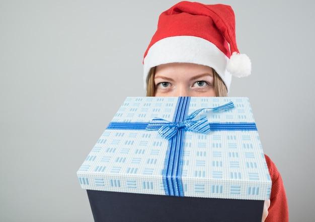 Молодая женщина в новогодней шапке с подарком