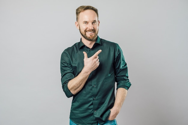 Портрет веселый молодой человек улыбается, указывая пальцем