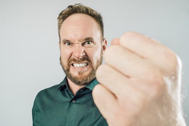 Красивый взрослый человек, показывая кулак с сердитым выражением