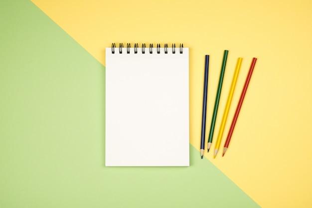 Вид сверху пустой блокнот с цветными карандашами