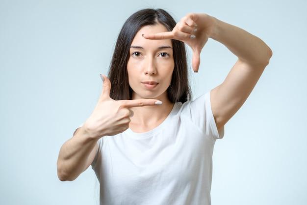 彼女の手を使用して境界線を作成する魅力的な若い女性