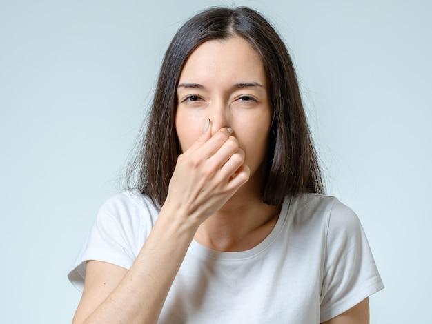 女の子は何かが臭いことを示す手で鼻をカバーします