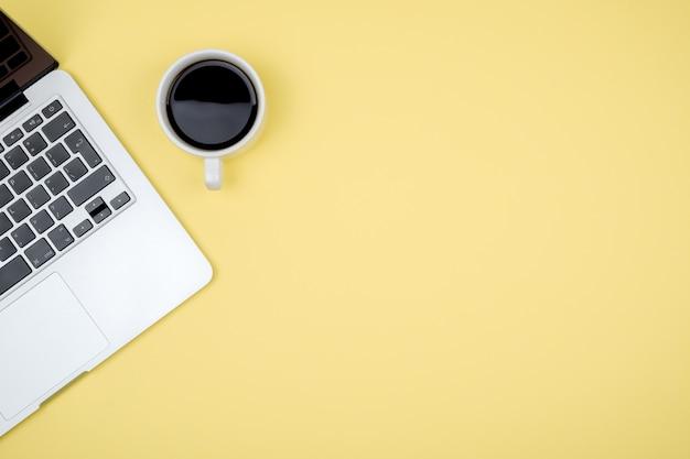 ラップトップコンピューターとコーヒーカップのオフィスデスク黄色テーブルの背景