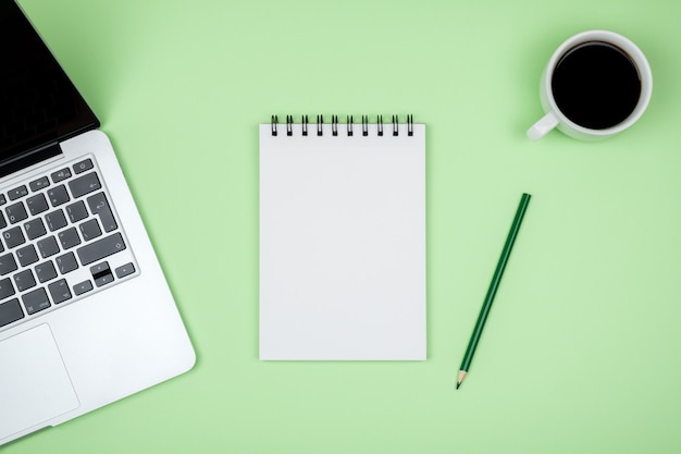空白のノートブックページ、ラップトップコンピューター、コーヒーカップとモダンなデザイナーオフィスデスクテーブル