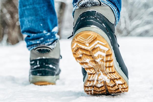 雪の中を歩きます。冬の靴のクローズアップ