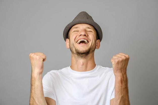 勝利ジェスチャーで彼の腕を持つ幸せな若い男
