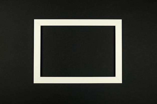 Рамка для фотографий лежит на текстурированном фоне бумаги в пастельных тонах