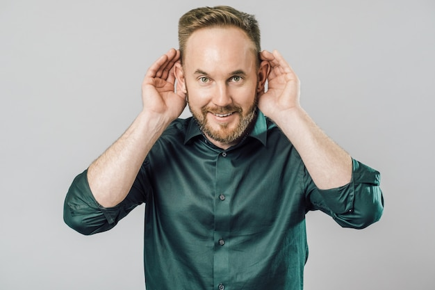 Человек с рукой над ухом, слушая и слушая слухи или сплетни