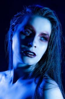 芸術的なメイクアップを持つ女性の青い肖像画