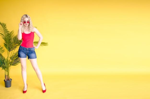 ファッショナブルな女性は赤いシャツとジーンズのショートパンツを着る