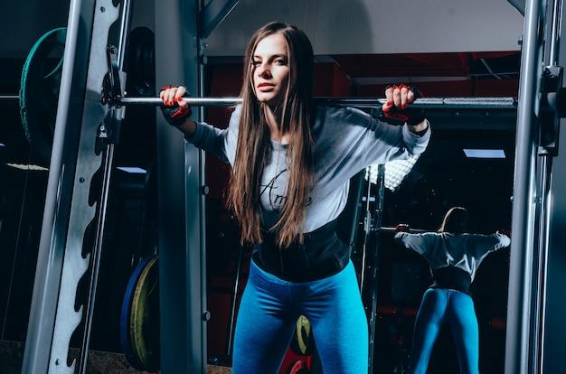 Красивая фитнес-девушка стоит возле штанги в современном фитнес-центре