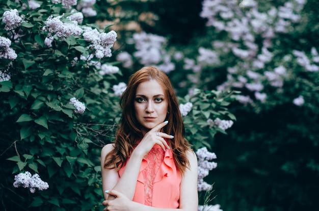 咲くライラックと春の庭で美しい女性