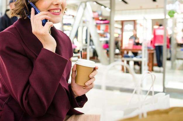 Обрезанный снимок красивой женщины. покупки в торговом центре. улыбаясь привлекательная женщина в фиолетовом пальто с кофе, чтобы пойти
