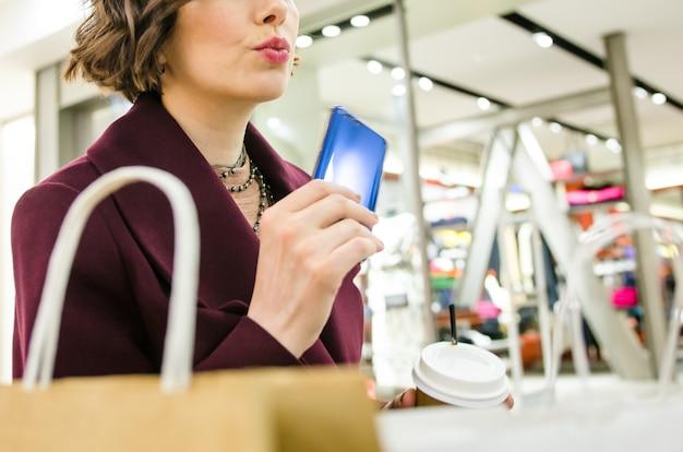 Покупки в торговом центре. привлекательная женщина в фиолетовом пальто с синим телефоном