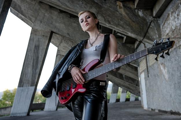 Молодая женщина рок-звезда с красной бас-гитарой