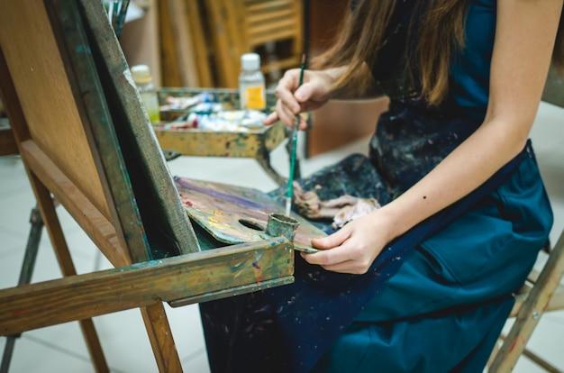 油絵の具でキャンバスにペイントアーティストの手