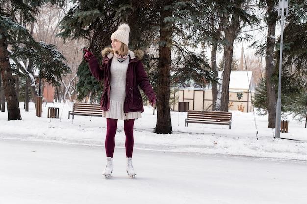 Симпатичная белокурая девушка на фигурных коньках на открытом катке в снежном зимнем парке. концепция зимних каникул