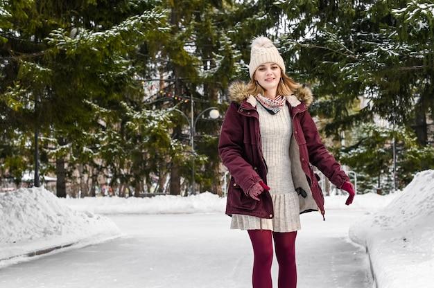 Улыбающиеся женщина в теплой одежде, имеющие прекрасное время кататься на коньках в парке снежной зимой. концепция зимних каникул