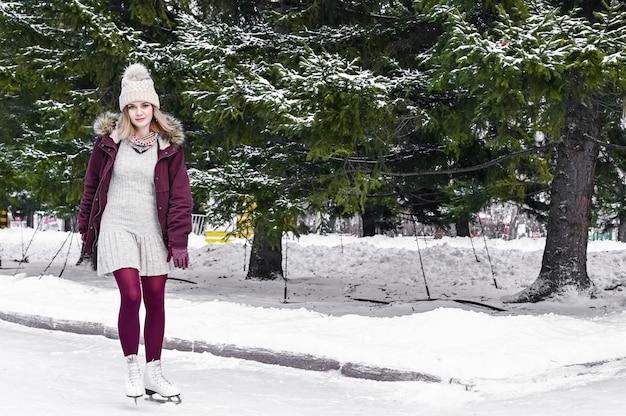Молодая белокурая кавказская девушка в теплой одежде катаясь на коньках на замороженном озере в парке снежной зимы. концепция зимних каникул