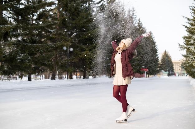 Молодая белокурая девушка катаясь на коньках в снежном парке зимы. концепция зимних каникул