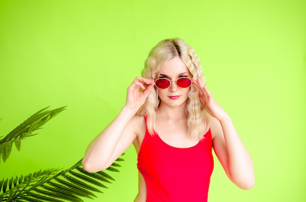 Портрет красивой белокурой девушки в солнечных очках и красном купальнике
