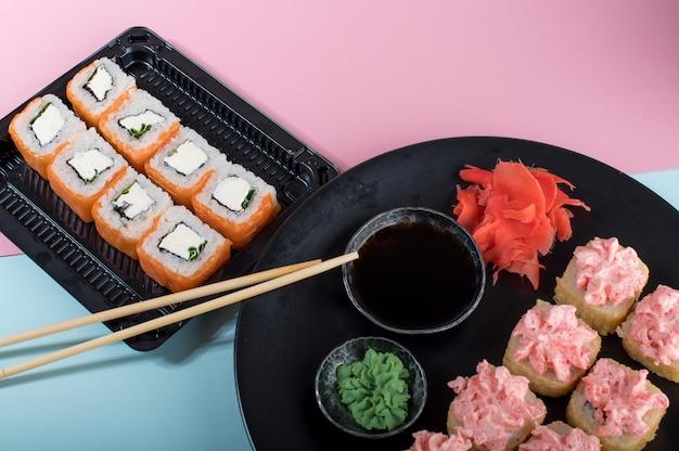 Суши роллы с соусом из красного майонеза и филадельфией на черной тарелке. розово-синий стол