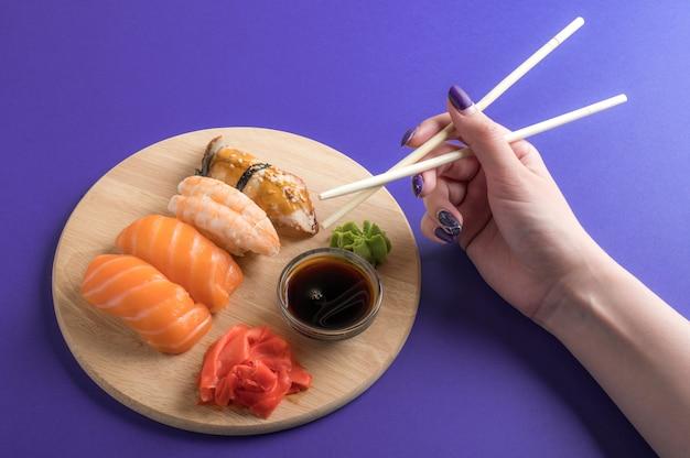 Аппетитный аппетитный суши-нигири сервируется на деревянных тарелках с соевым соусом.