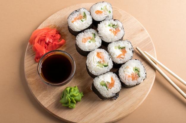 Набор суши роллов подается на деревянной доске