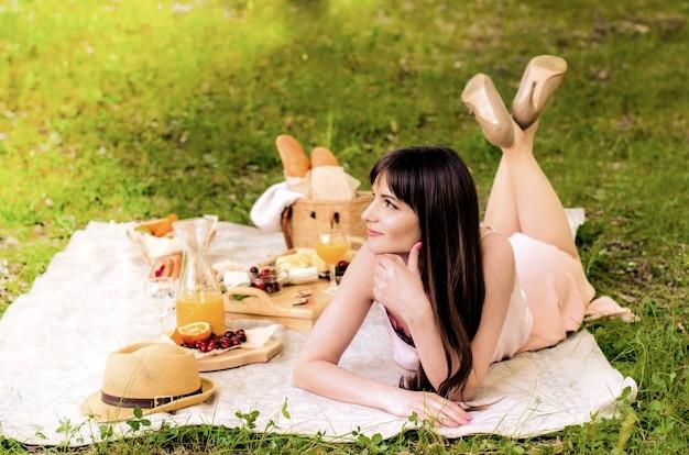 晴れた日にピクニックを持つかなり若い女性