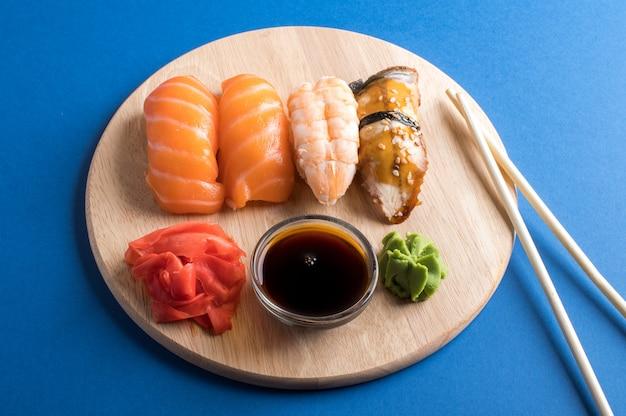 Аппетитный аппетитный суши-нигири сервируется на деревянных тарелках с соевым соусом и палочками для еды. квартира лежала на синем столе