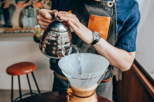 Бариста наливает кипящую воду из чайника