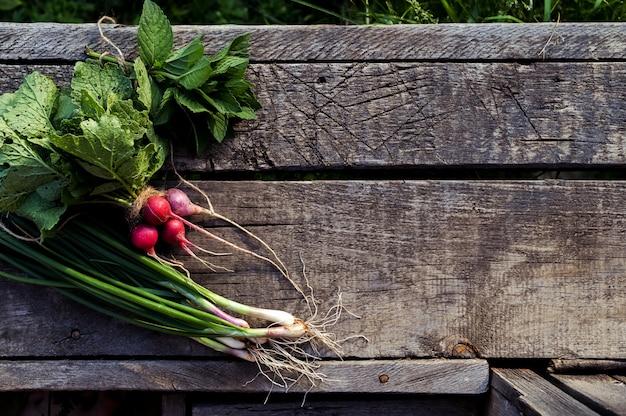 古い木製のテーブルに新鮮な野菜。木製の背景に有機食品。セレクティブフォーカス