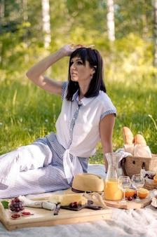 Улыбается молодая девушка в парке, держа напиток, имея летний пикник в парке на открытом воздухе. здоровая еда, расслабляющая концепция