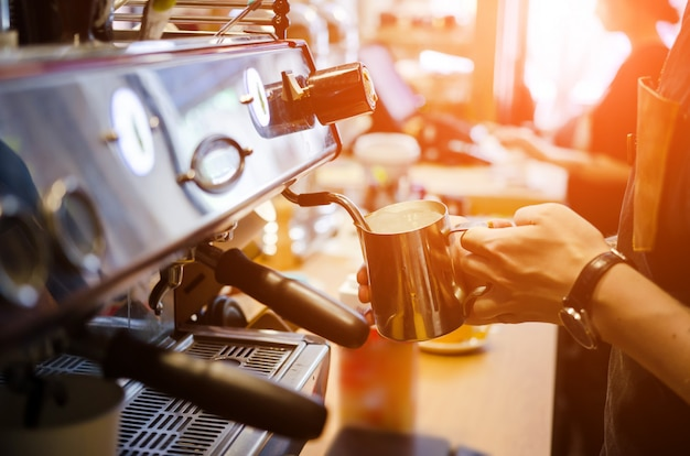 男性のバリスタは、コーヒーショップカフェでコーヒーカフェラテアートを作る