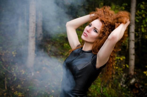 Чувственная женщина с рыжими вьющимися волосами в лесу