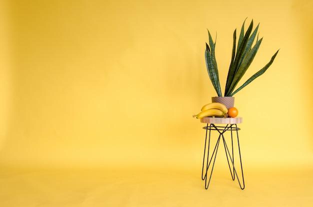 Стол с цветами и фруктами на желтом фоне