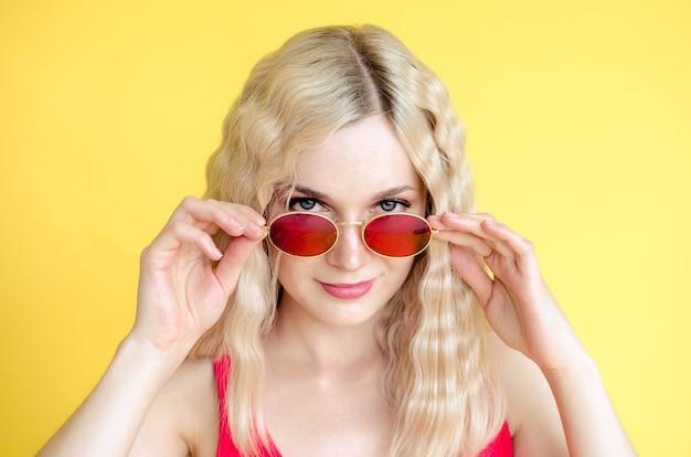 黄色の背景に赤いサングラスをかけている美しい若い女の子