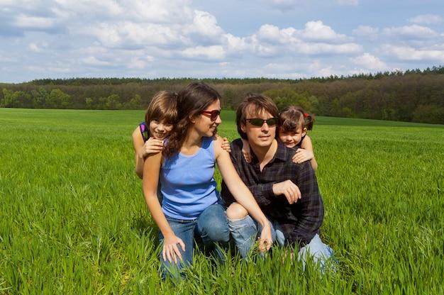 Счастливая семья с двумя детьми на зеленом поле