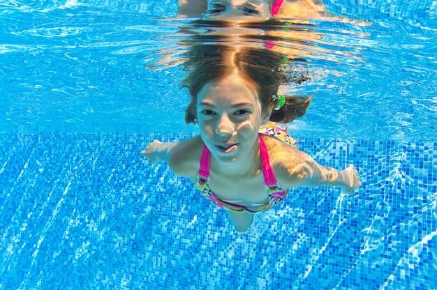 子供は水中プールで泳ぐ