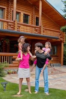 Счастливая улыбающаяся семья возле деревянного дома