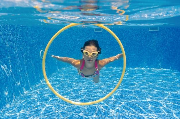 Ребенок плавает в бассейне под водой